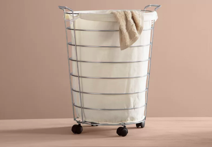 The white removable laundry basket in its silver wire basket