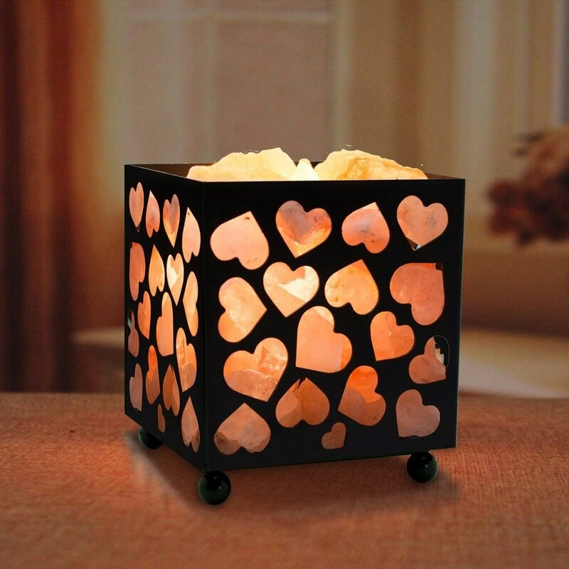 a black metal box with heart-shaped cutouts that's full of small Himalayan salt rocks. they're lit up.