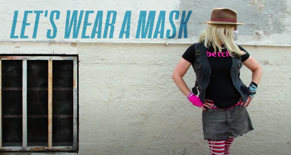 """Kelly in alley posing with a """"Let's Wear A Mask"""" written beside her in blue lettering"""