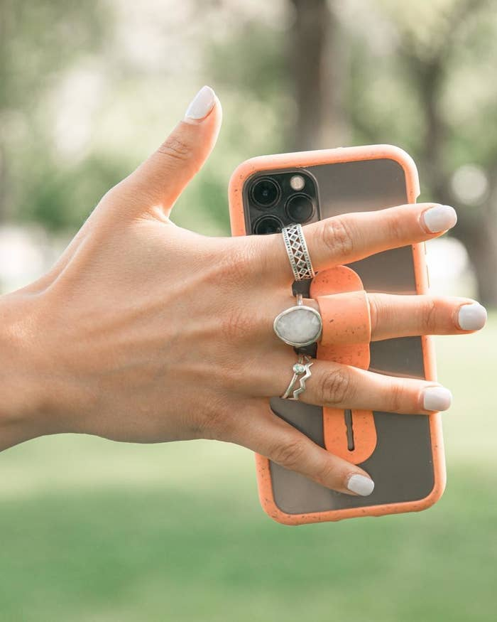 A person wearing several rings and holding their phone with the phone grip
