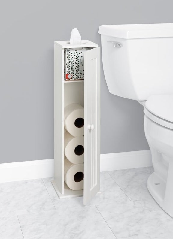 A white storage cabinet holding three rolls of toilet paper and a box of tissues