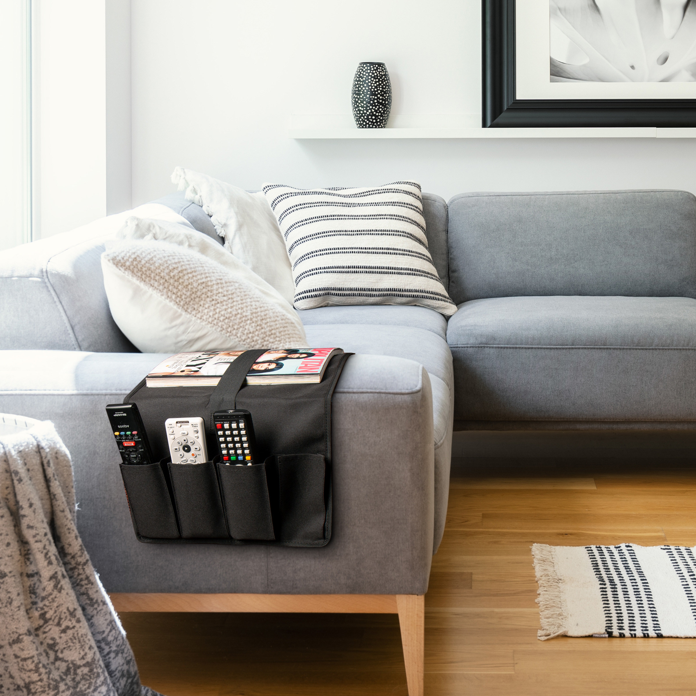 Remote caddy is resting on the arm of a couch, holding three remotes and a magazine