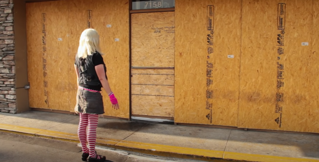 Kelly standing outside a boarded up store