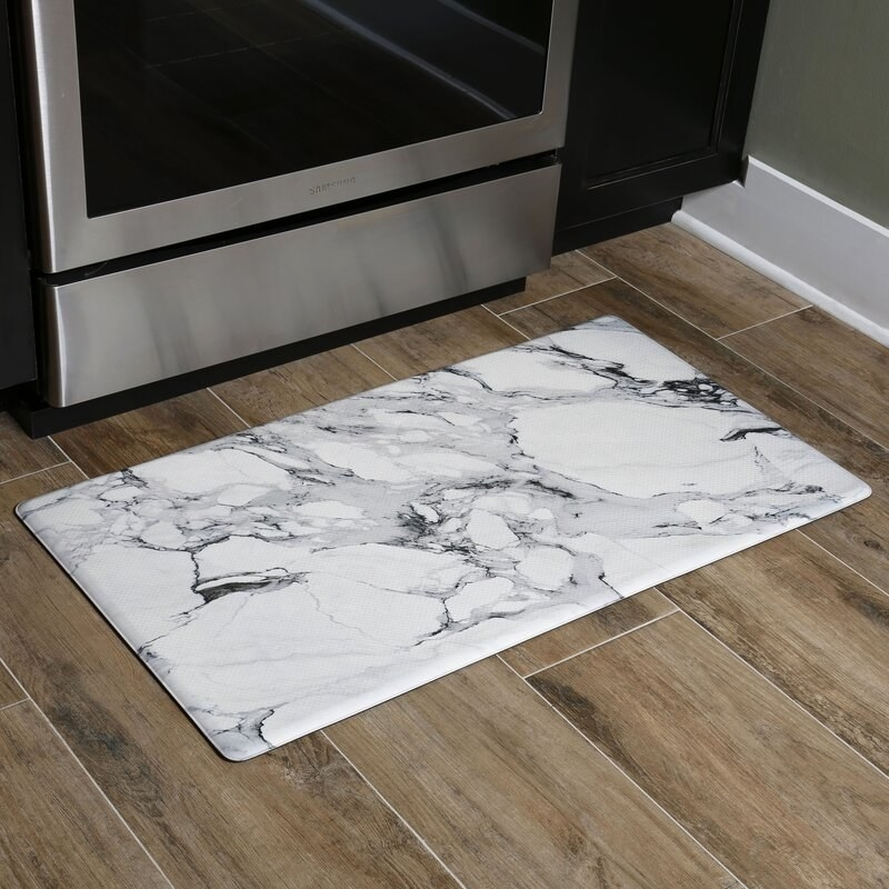 The black and white marbled anti-fatigue mat on wood kitchen floor