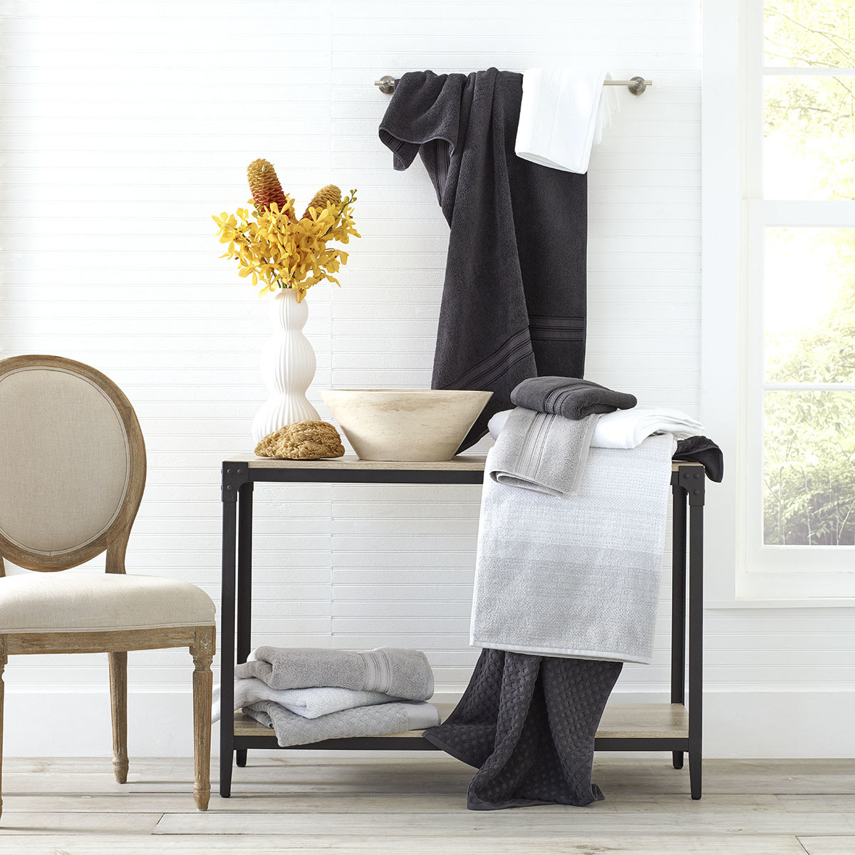 white, black, and grey towels on a shelf