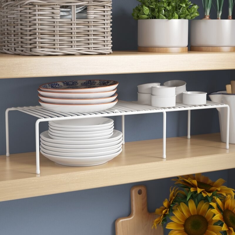 The white kitchen cupboard shelving rack with plates on top of and beneath it