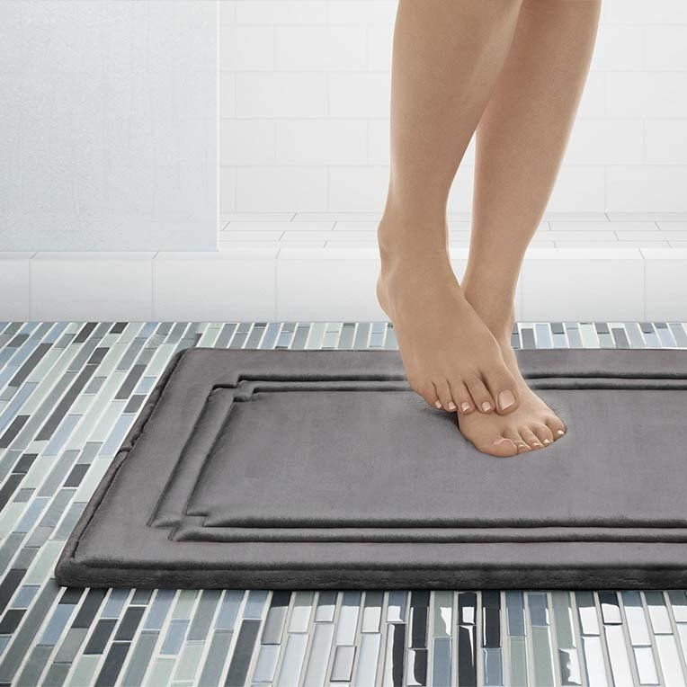 a person standing on a grey floor mat in a bathroom