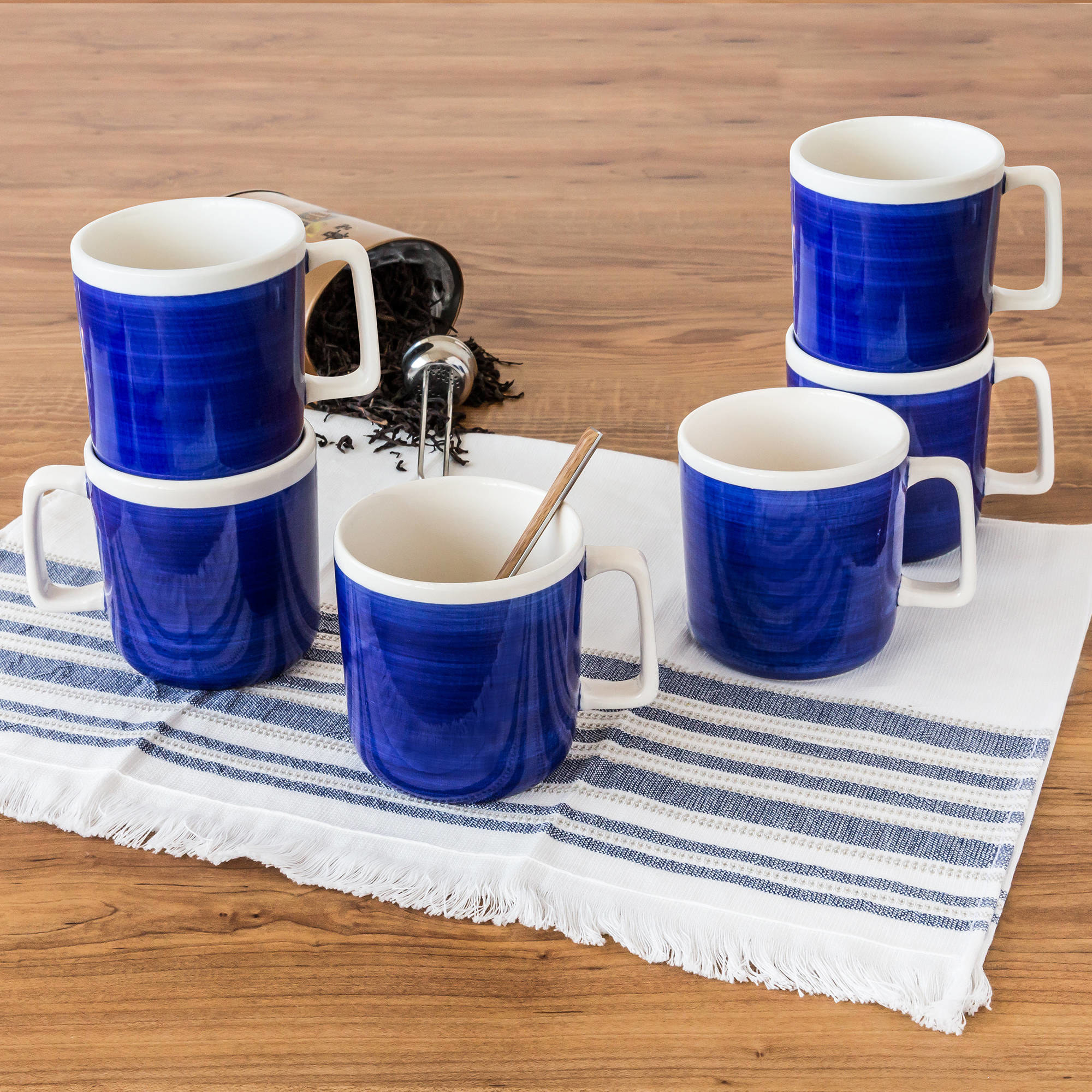 six indigo mugs with white rims and white handles