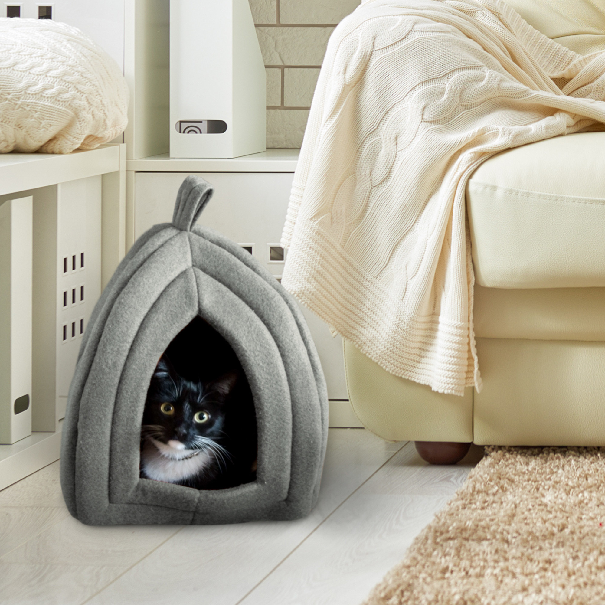 A tuxedo cat in a grey pet tent