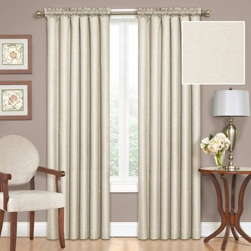 A set of ivory curtains hung in front of a window