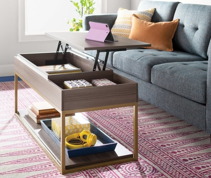 A gray wood coffee table with a lift-top and brass legs