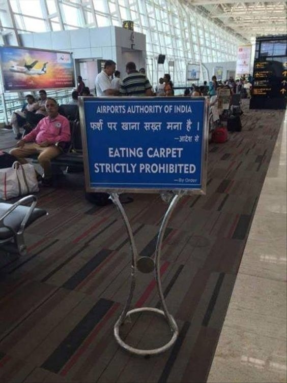A busy airport in india and a sign in the terminal reads eating carpet strictly prohibited
