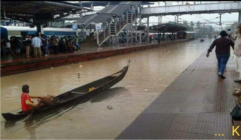 a man sails on a canoe on waterlogged railway tracks
