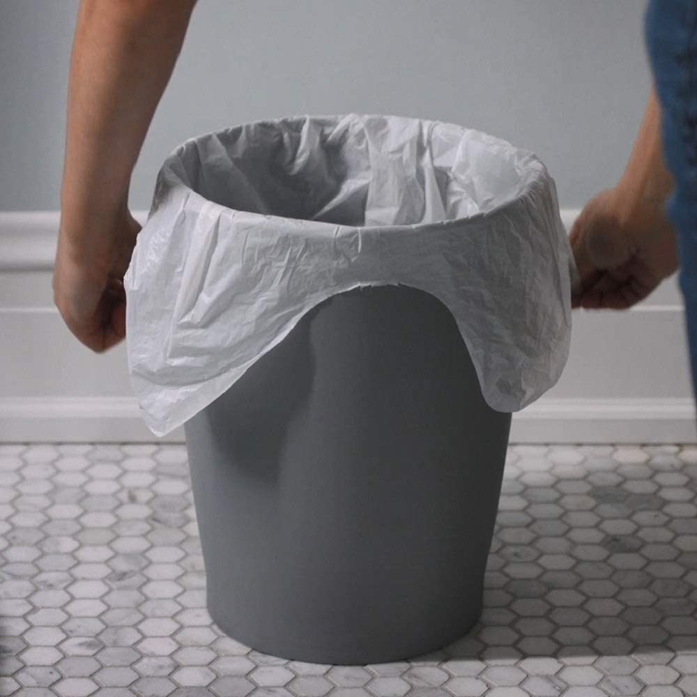 A person puts a trash bag in a trash container