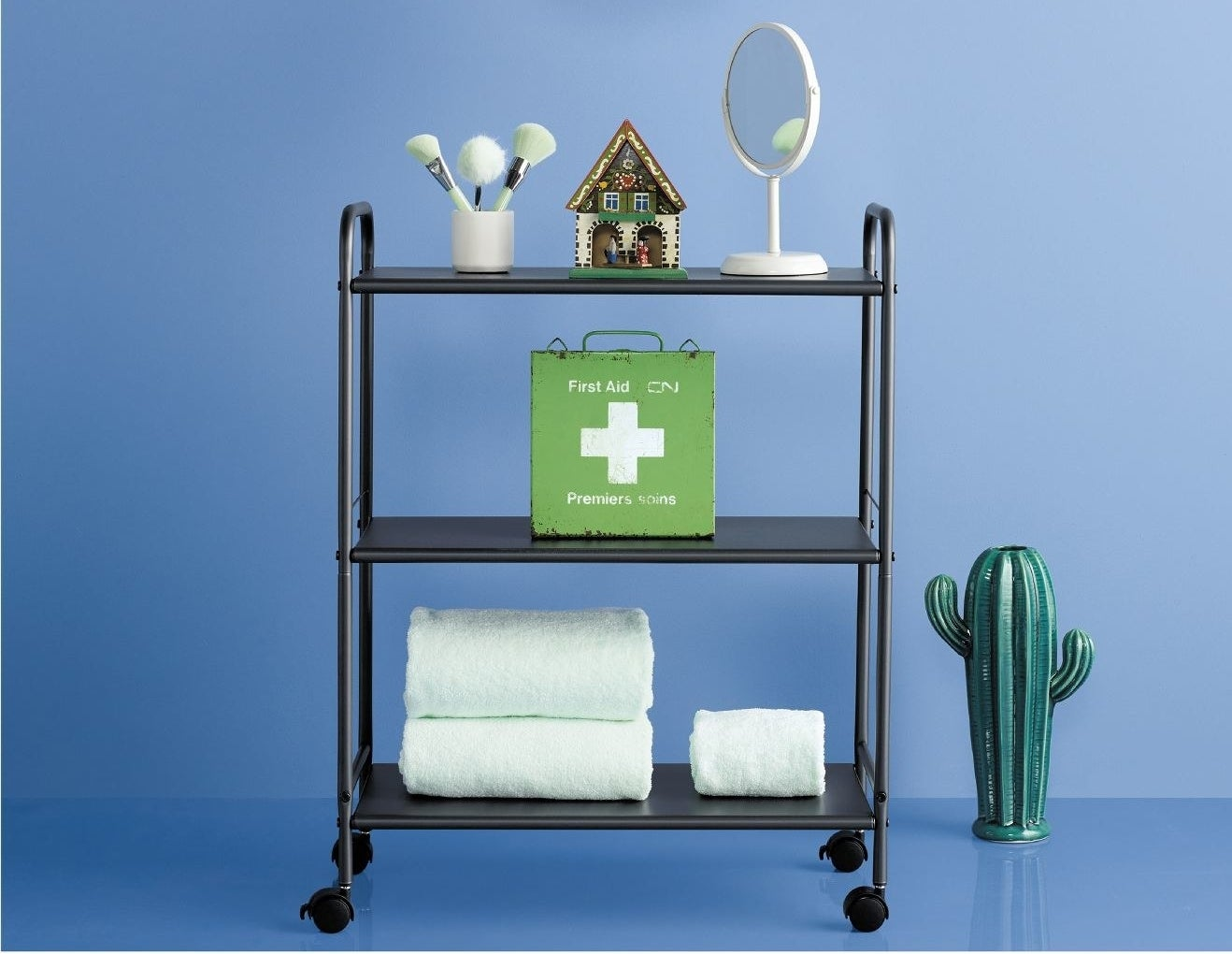 Black cart with towels and bathroom items on it