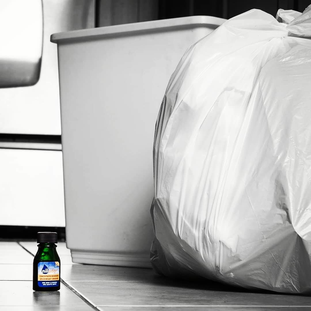 A bottle of the product sits beside a garbage pail and garbage