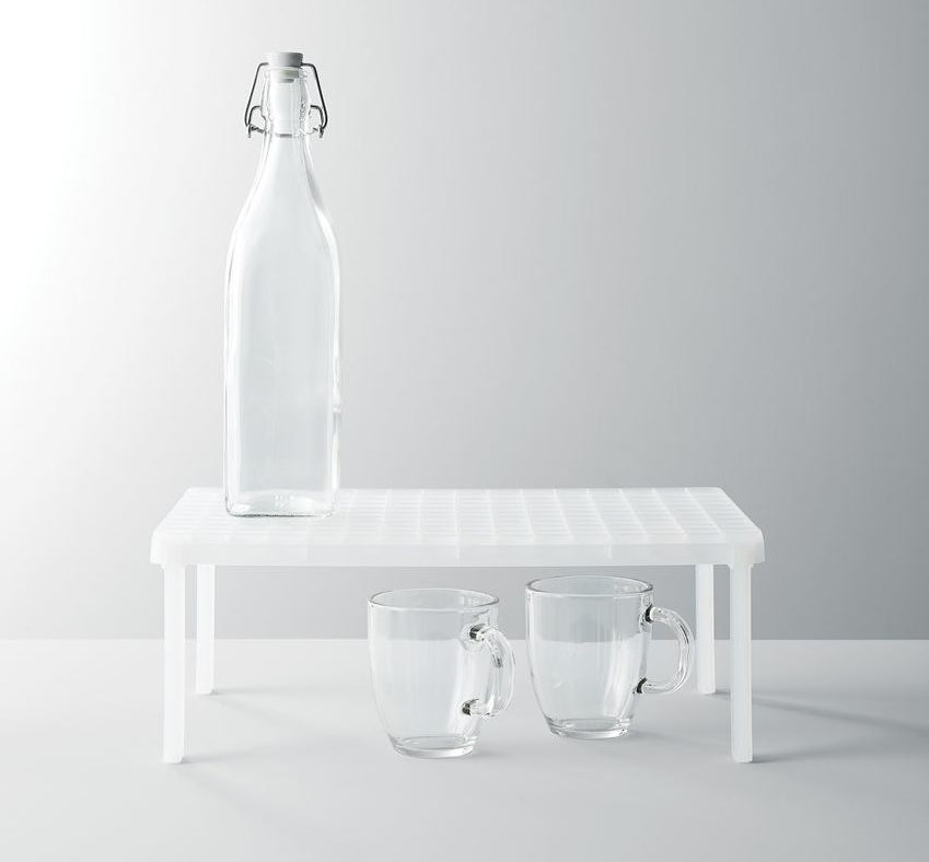 Product with mugs under it and a water bottle on top