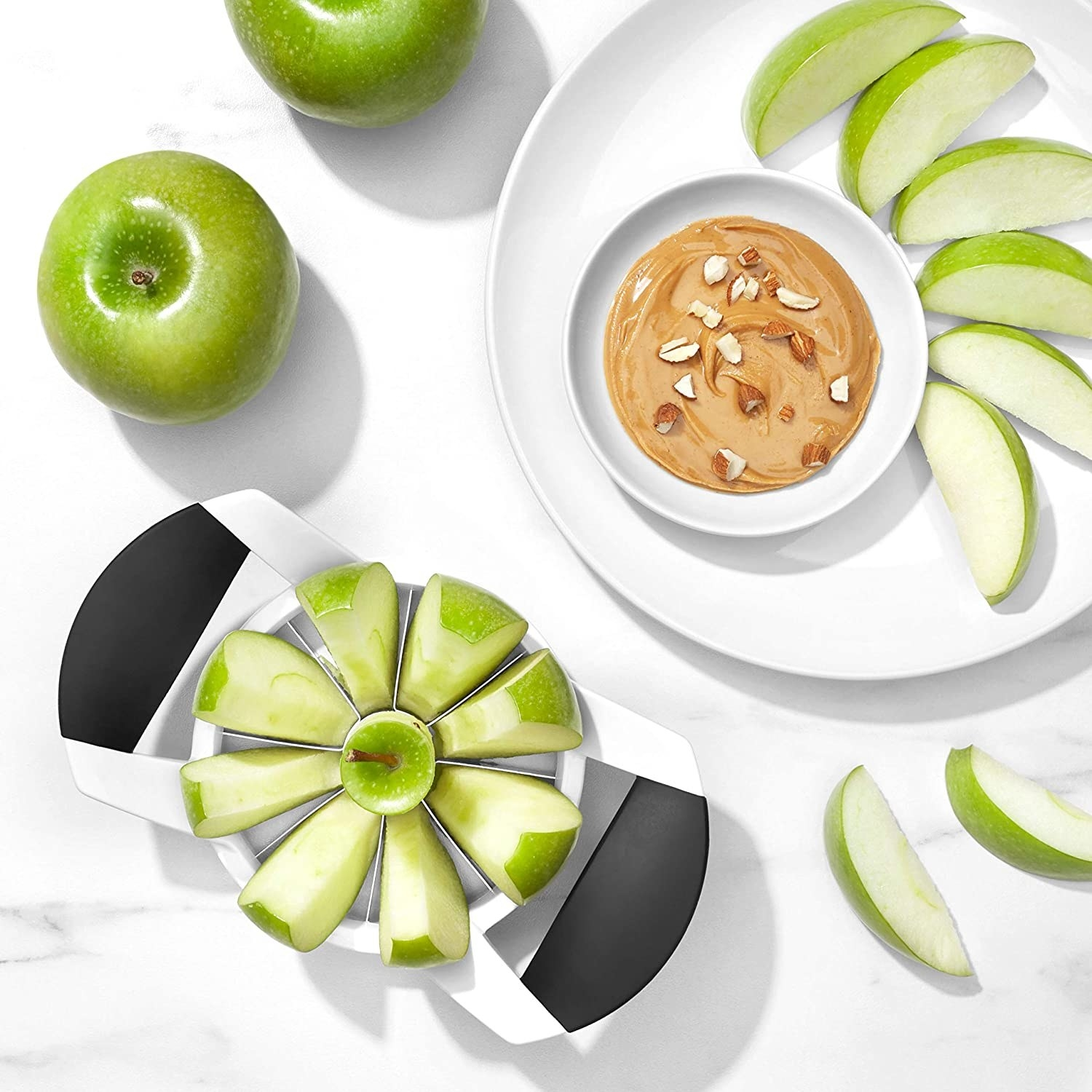 An apple in the slicer next to a plate of apple slices and peanut butter