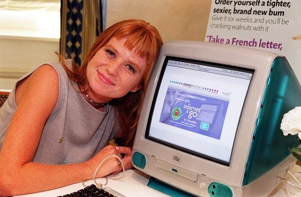 red haired young woman with head on a computer
