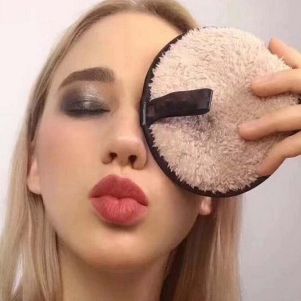 A person holding a makeup-covered cleansing puff in front of their eye