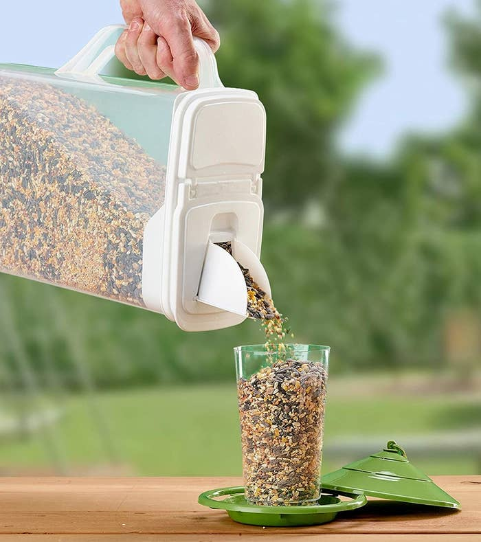 A person using the pet food bin to pour bird seed into a glass