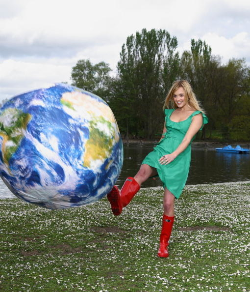 woman in red wellington boots and green dress kicking an inflatable earth.