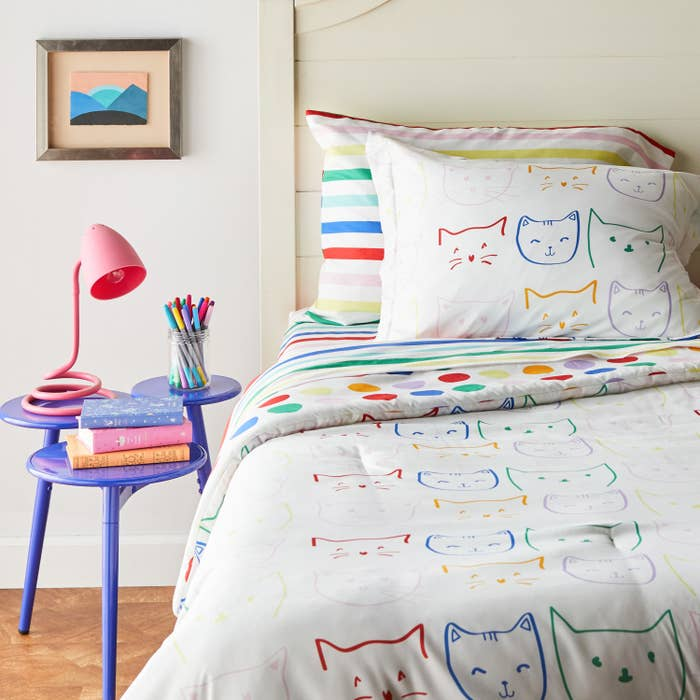 Red, blue, green, pink, purple, and yellow sketches of cat faces on white bedding