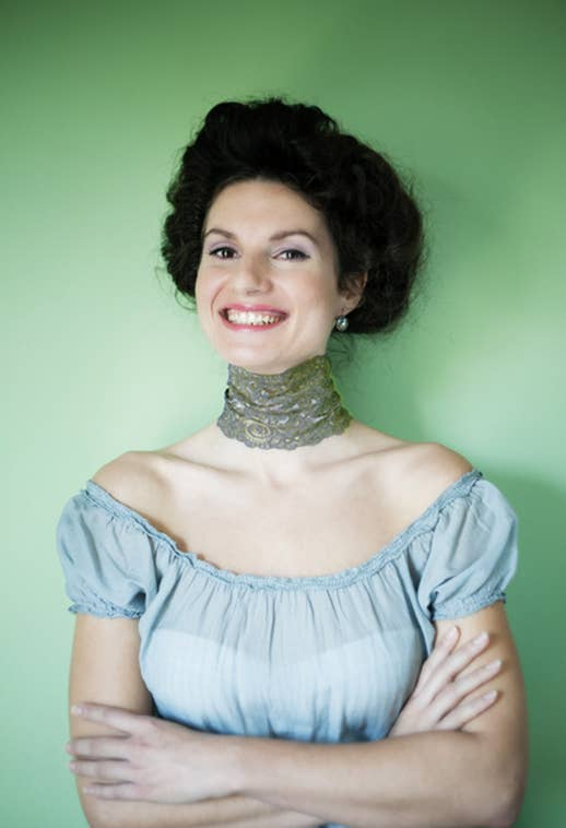 A woman smiling with a thick green choker
