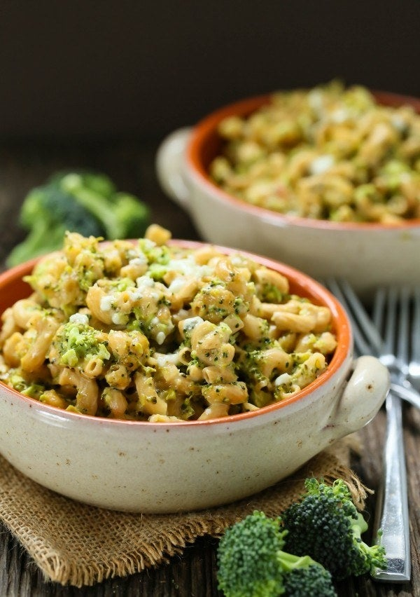 Two bowls of mac 'n' cheese with tiny pieces of broccoli mixed in.