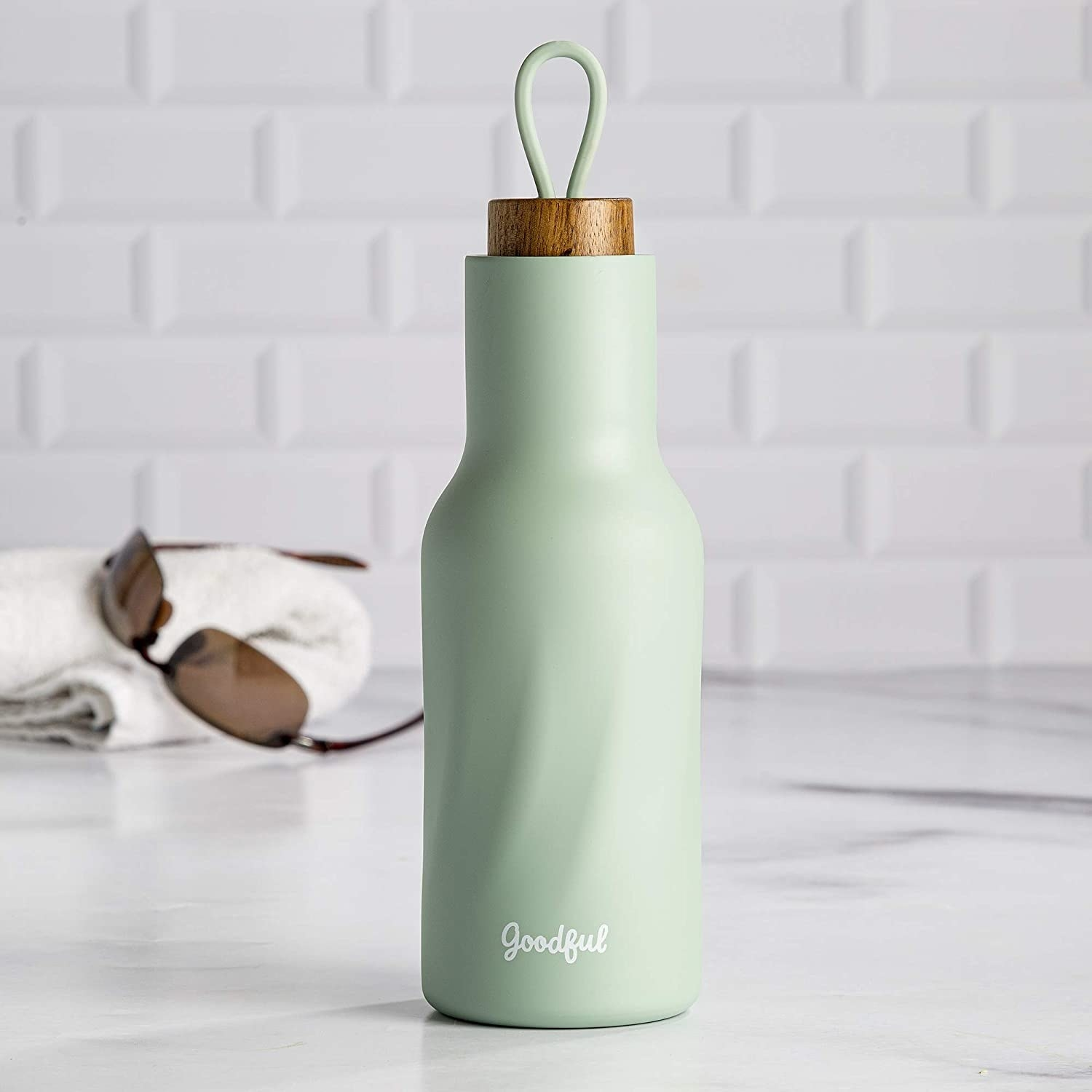 mint green water bottle with faux wood top with a loop