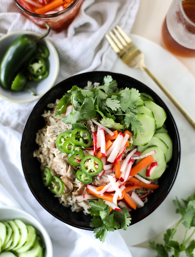 A rice bowl topped with pork, thinly sliced radishes and carrots, cucumbers, jalapeño, and cilantro.