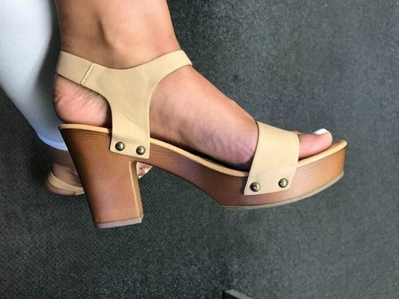 Reviewer wearing the wooden heeled sandals with faux leather straps