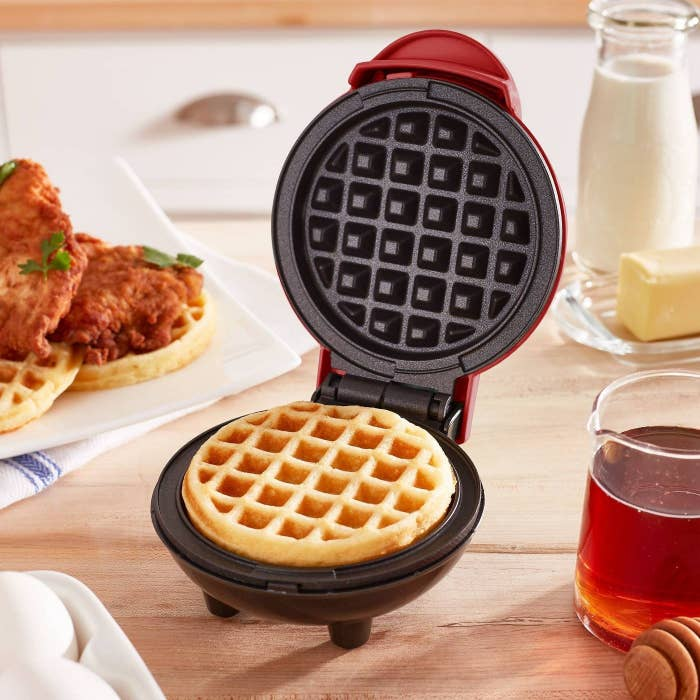 mini red waffle maker on a table top with chicken and waffles in the background
