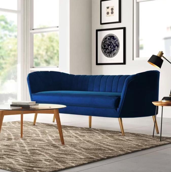 Dark blue velvet flared arm sofa next to wooden coffee table