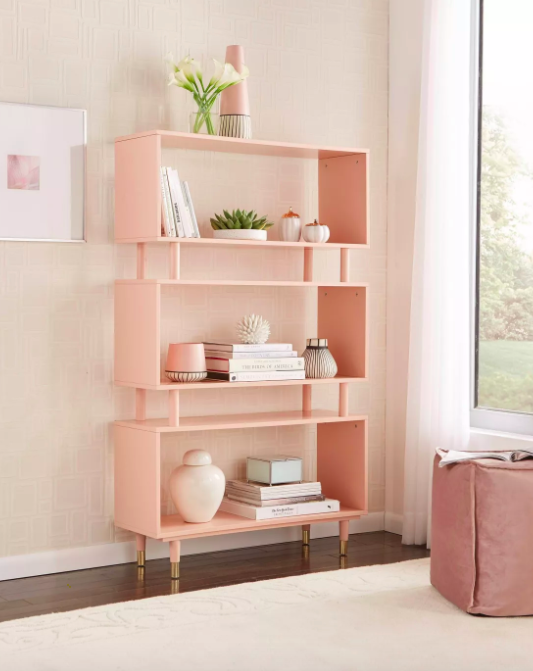 Light pink bookcase with a mod-inspired design against a cream-colored wall