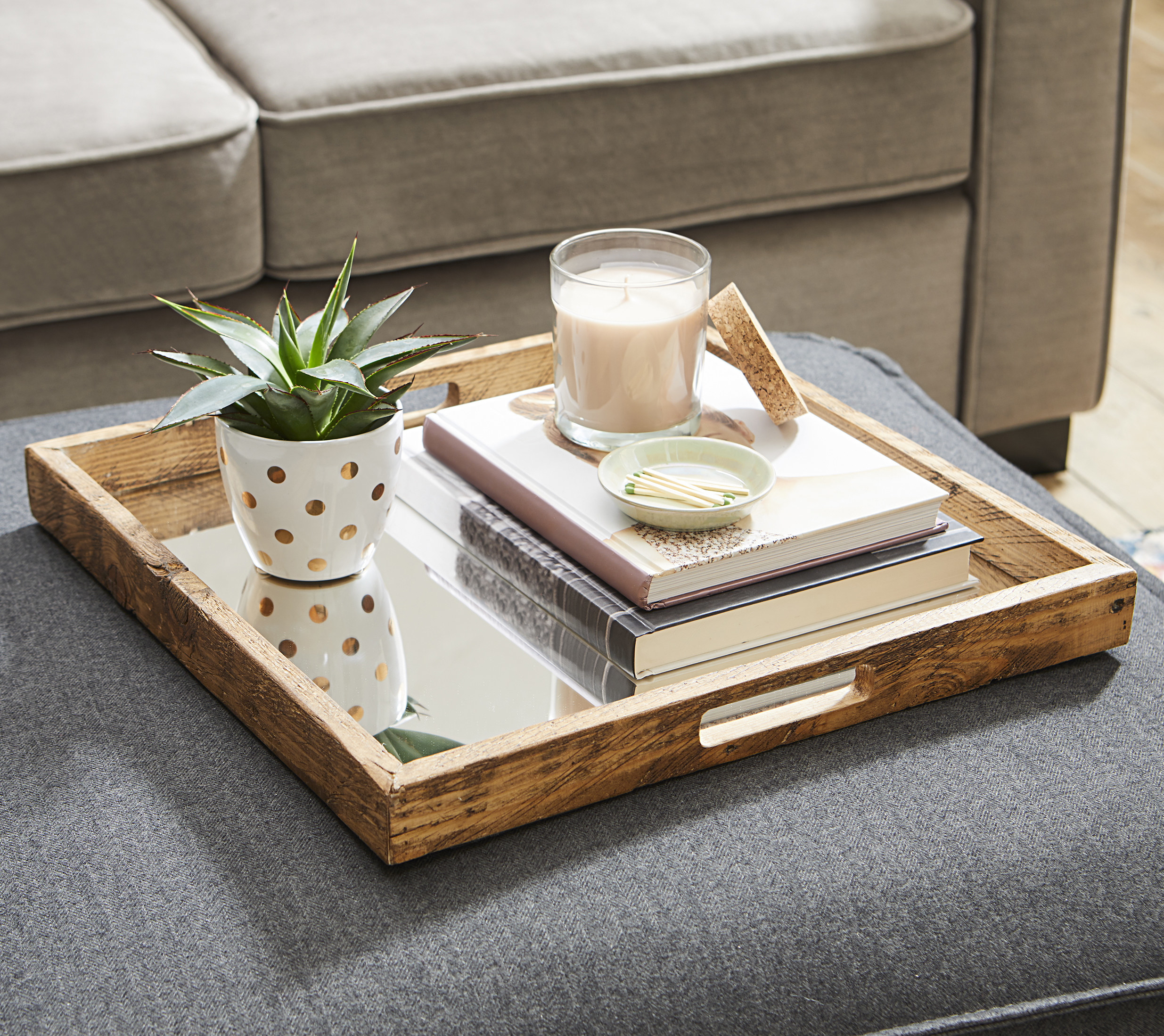 The decorative tray sitting on top of an ottoman, featuring a plant, books, and a candle.