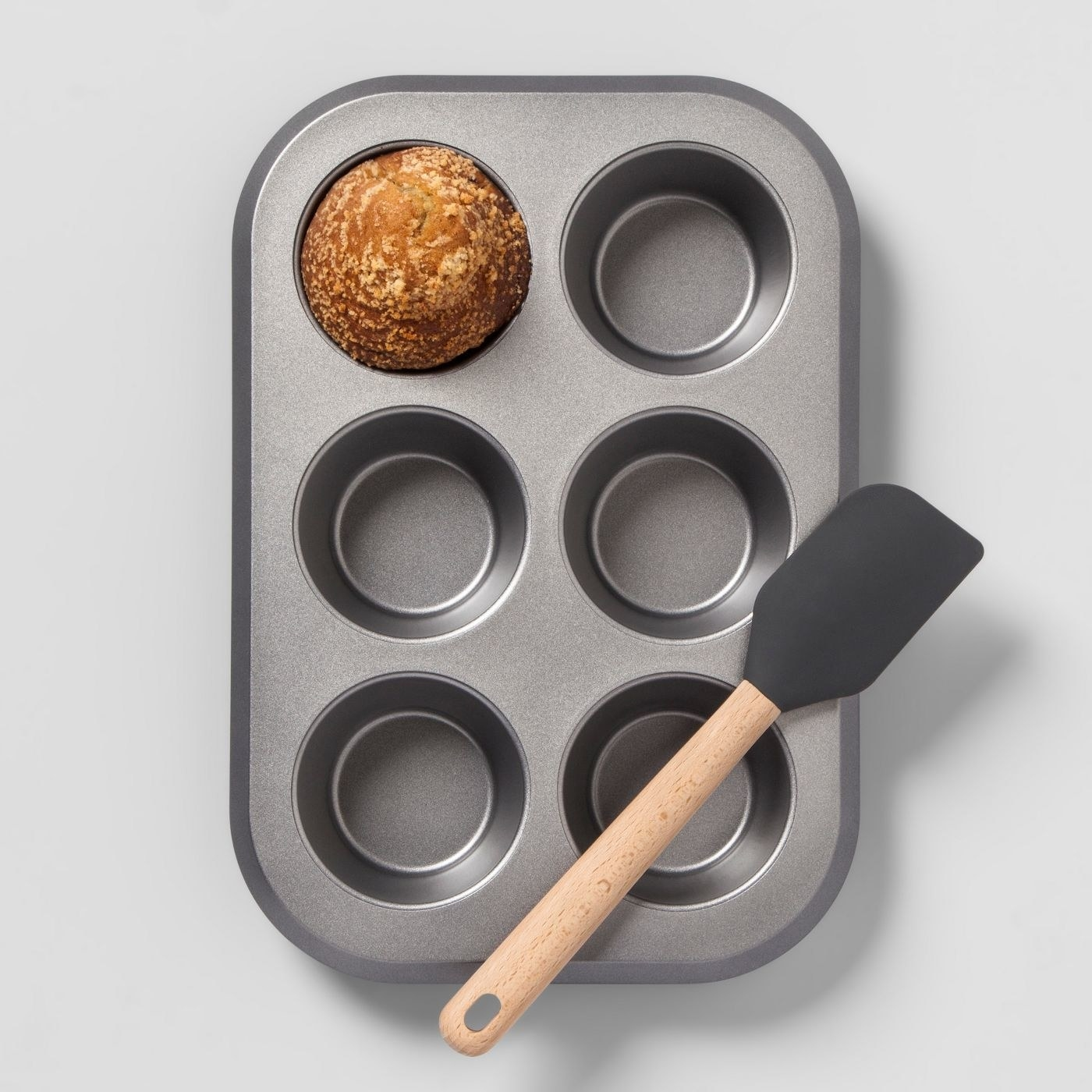 jumbo muffin tin with one muffin in it and a spatula on top