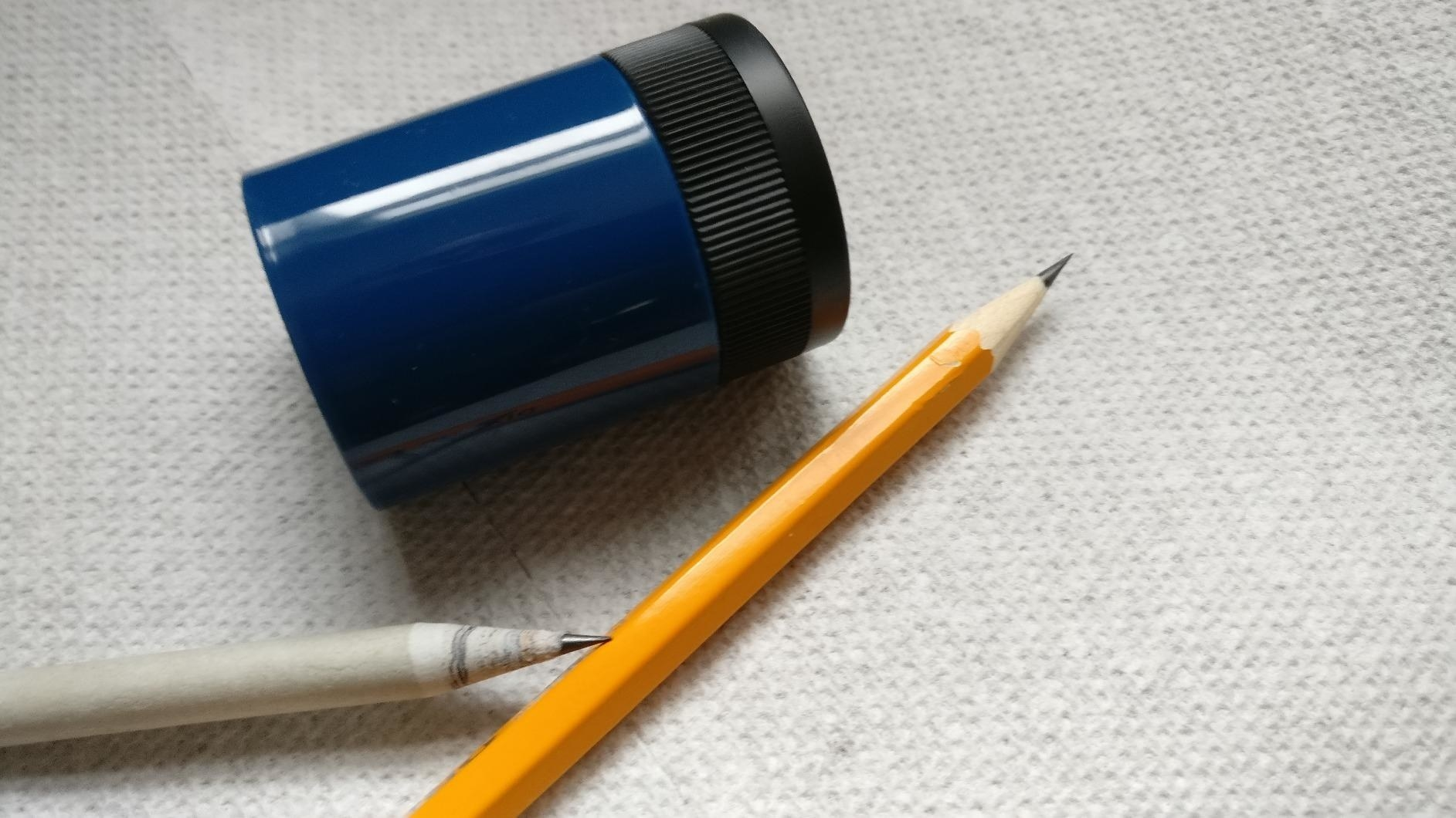 A blue plastic pencil sharpner with a black top next to some sharpened pencilse