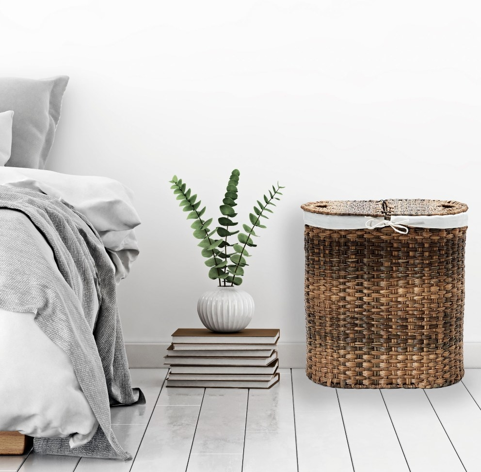 The wicker laundry basket next to a plant held up by a stack of books
