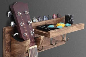 A guitar wall hanger holding a guitar, a capo, some fingerpicks, a clip on tuner, and some guitar picks.