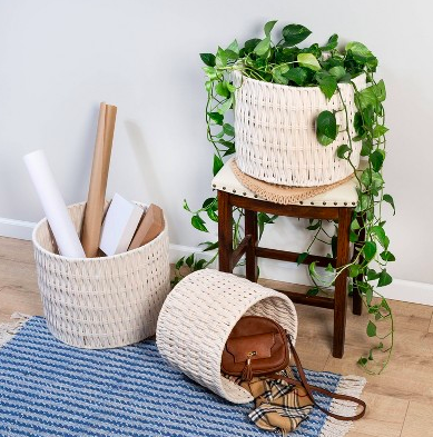 Three white woven baskets filled with plants, accessories, and posters on a hardwood floor