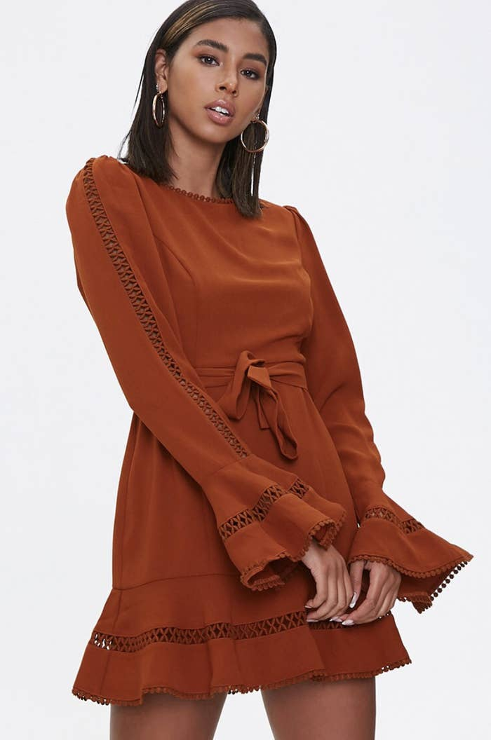 Model in a rust orange long-sleeved mini dress with a tie waist and bells on the sleeves
