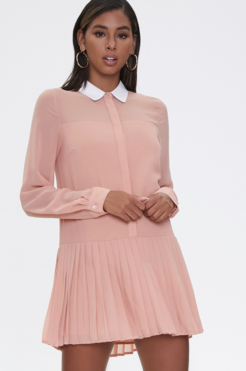 Model in a pink collared shirt-dress with a pleated skirt