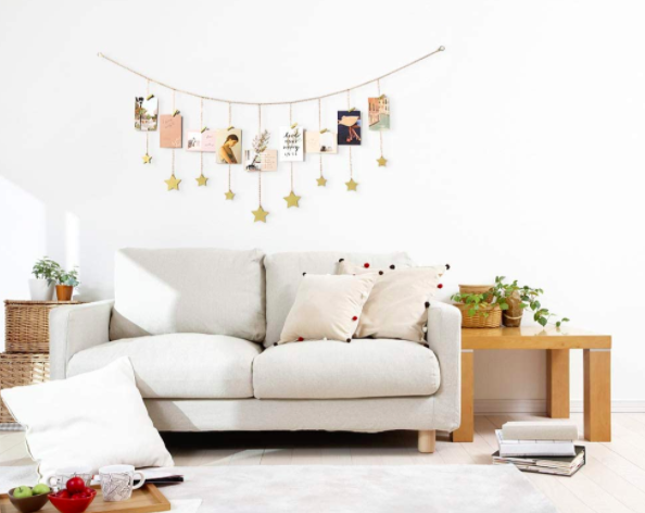 Gold, star-detailed hanging photo display with photos and postcards over a white couch