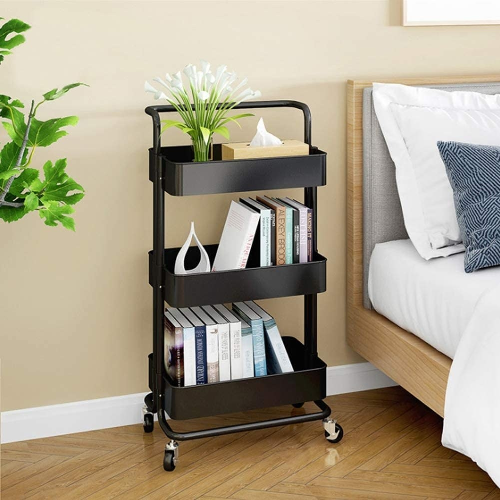A metal rolling cart with three tiers Two shelves have books and the top shelf has a box of tissue and a vase with flowers