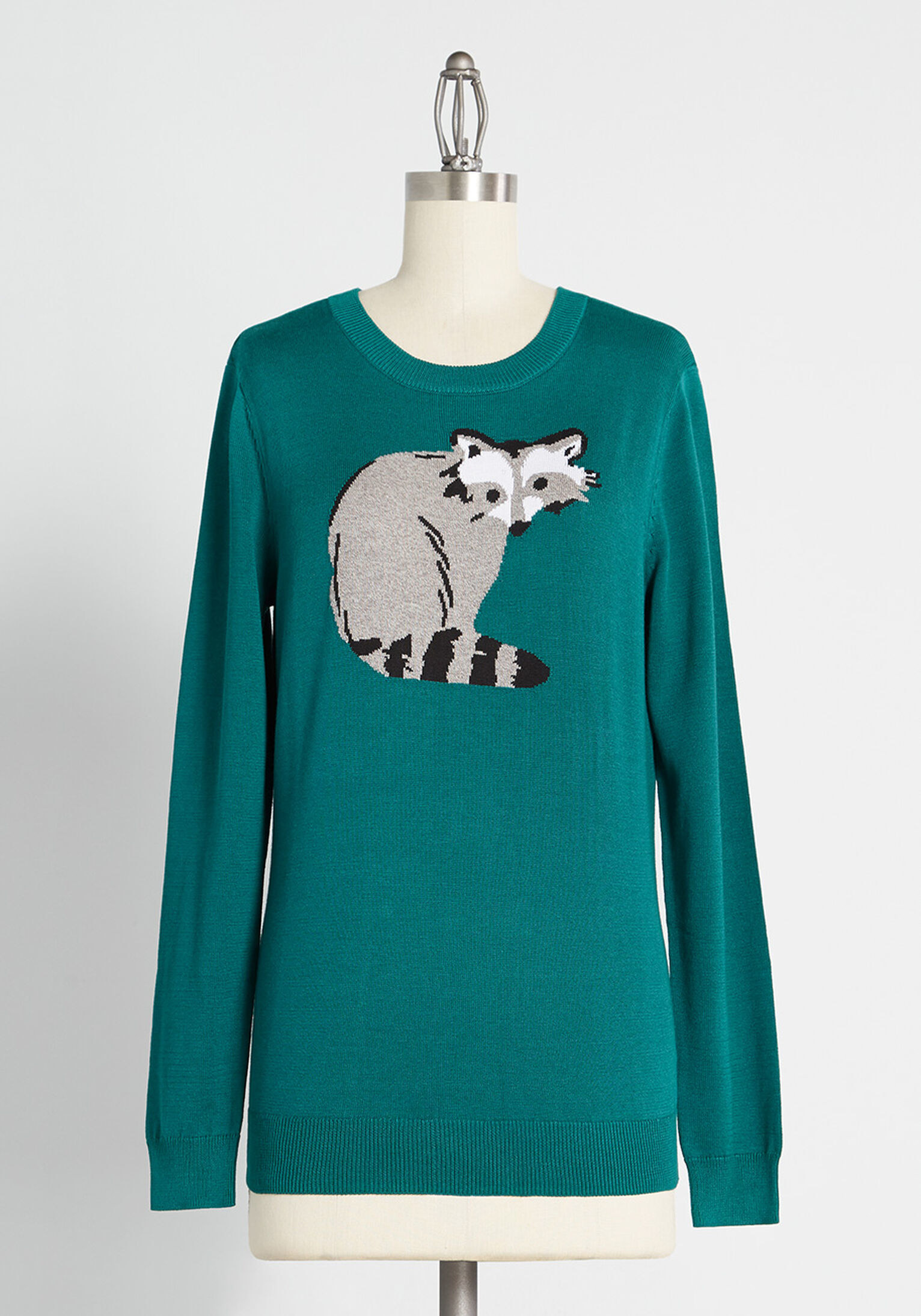 a teal sweater with a raccoon on it
