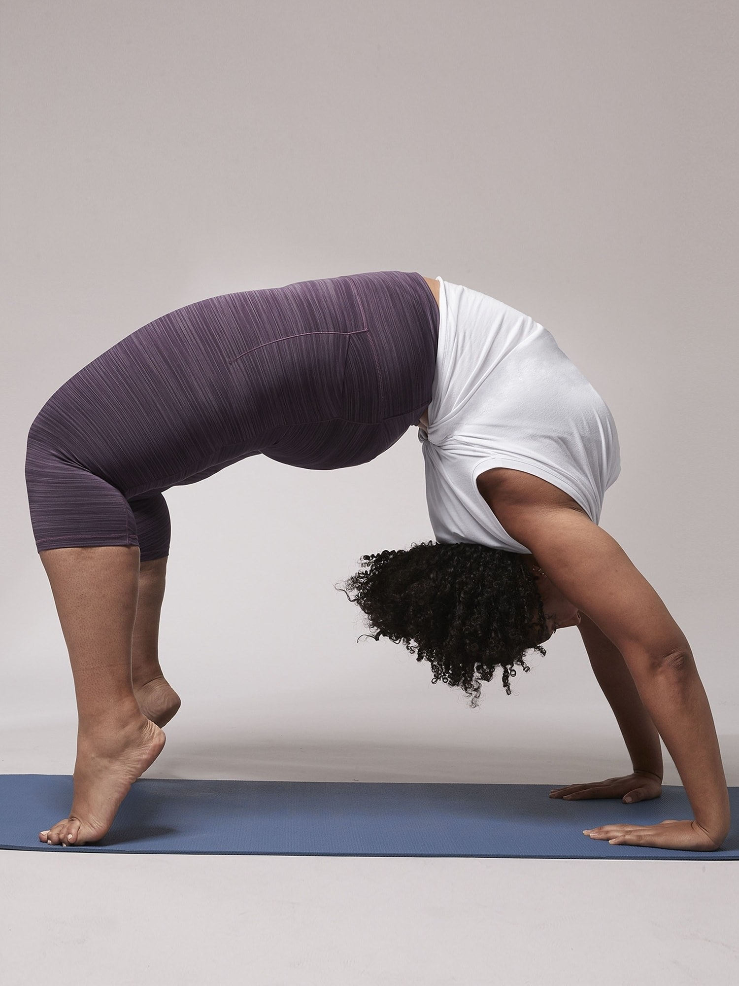 Model wearing the capri-length leggings in purple with a lined pattern to them while doing a backbend.