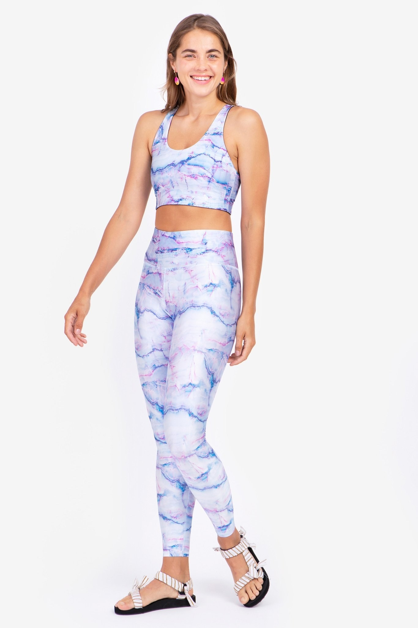 Model wearing the full-length high-waisted leggings with a blue and pink marble-like pattern all over them.
