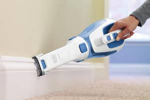 handheld vacuum cleaning a baseboard