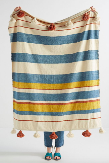 White, red, yellow, and blue-striped tassel blanket held up by model wearing jeans and turquoise shoes